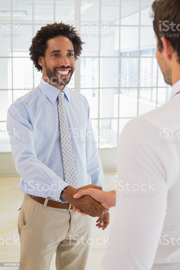 Smiling young businessmen shaking hands in office stock photo
