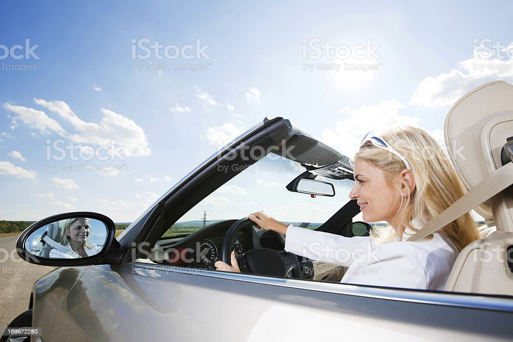 Smiling young businesswoman driving a convertible royalty-free stock photo