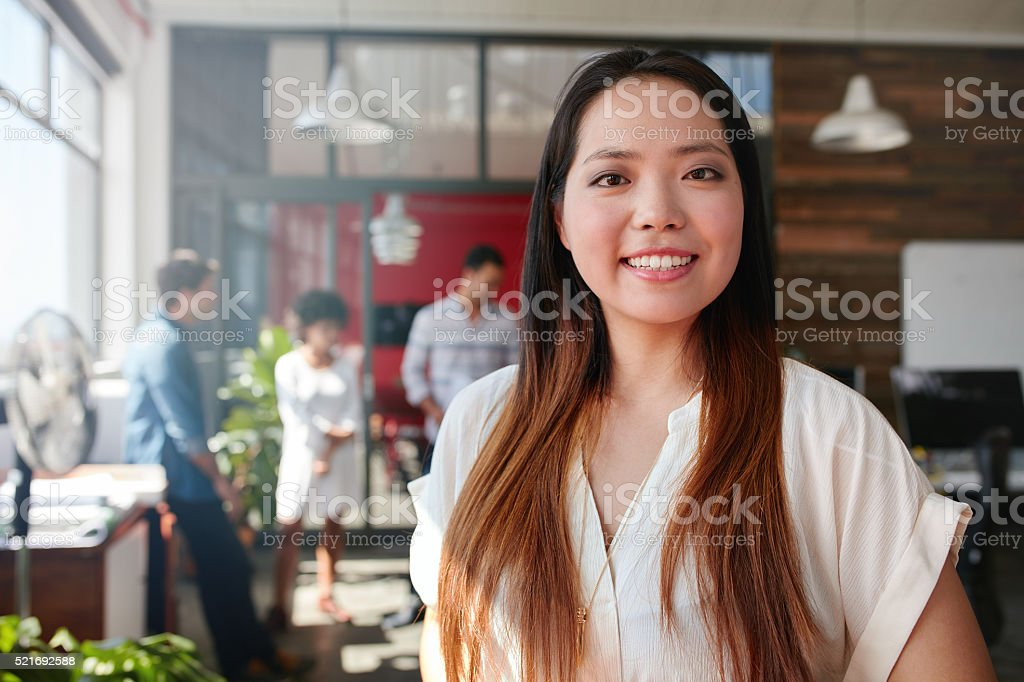 Smiling young businesswoman in office stock photo