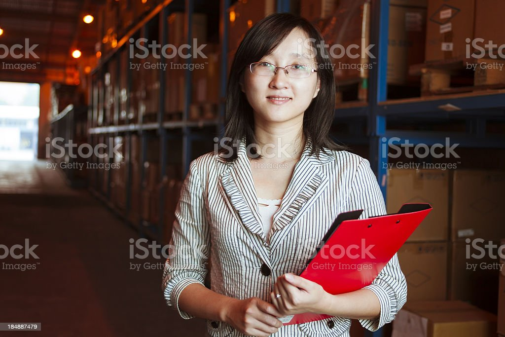 Smiling young businesswoman in warehouse royalty-free stock photo