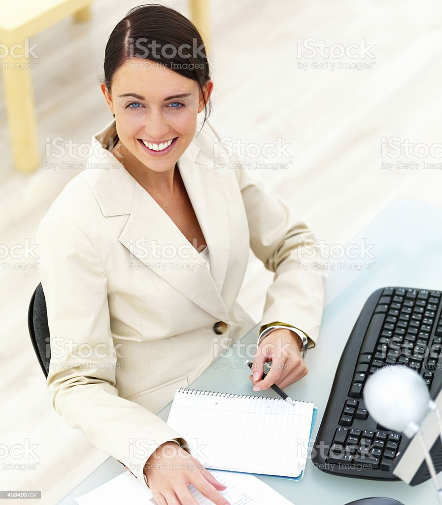 Smiling young businesswoman sitting by desk with computer and documents royalty-free stock photo