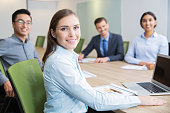 Smiling young businesswoman sitting in boardroom