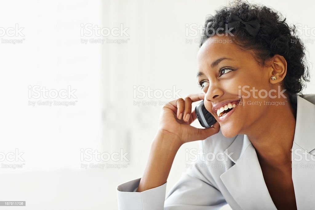 Smiling young businesswoman talking on a cellphone royalty-free stock photo