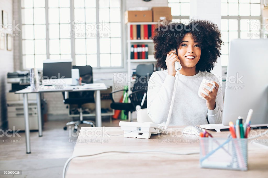 Smiling young businesswoman talking on the phone at workplace stock photo
