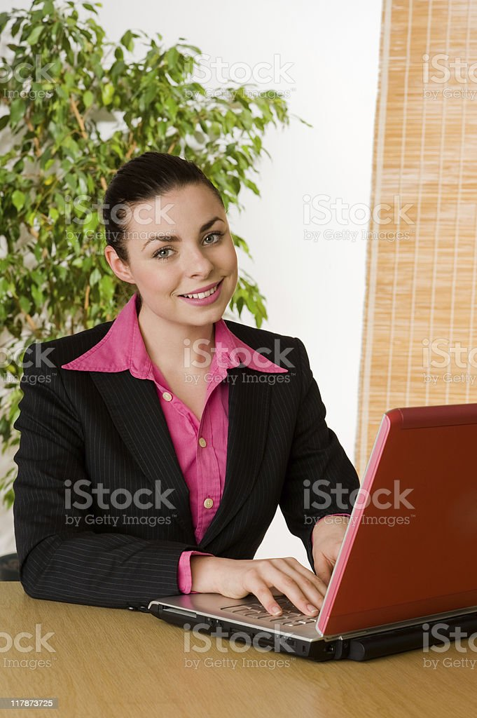 Smiling young businesswoman with pink laptop stock photo