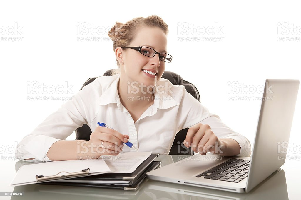 Smiling young businesswoman working at her desk royalty-free stock photo