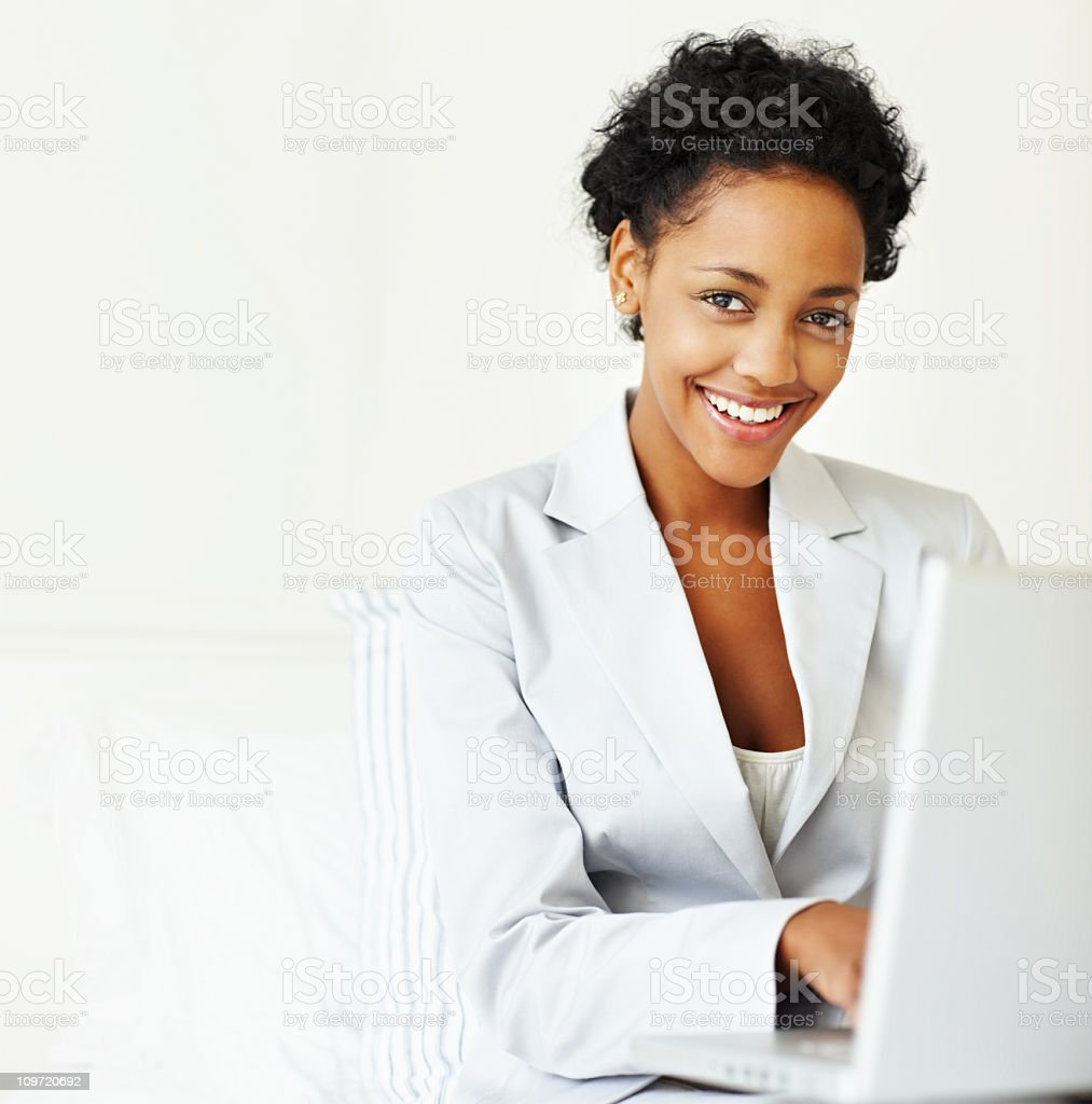 Smiling young businesswoman working on a laptop royalty-free stock photo