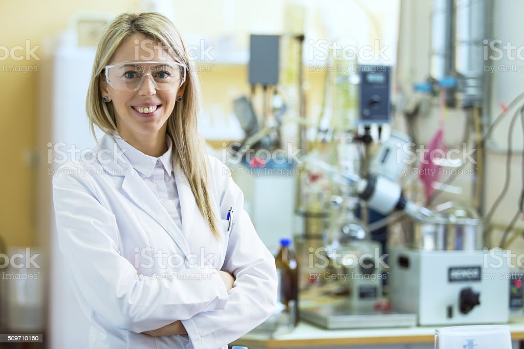 Smiling young chemist in chemistry lab stock photo