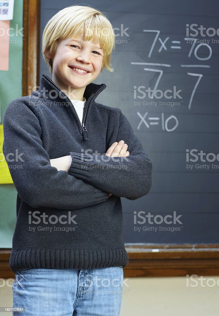 Smiling young confident boy standing against the blackboard royalty-free stock photo