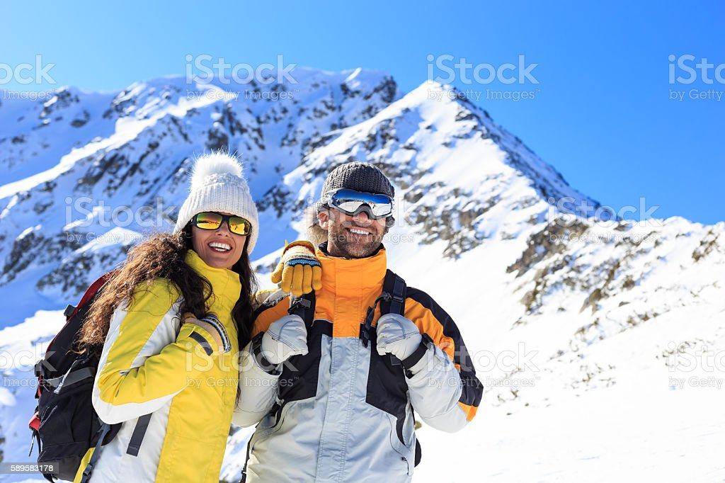 Smiling young couple backpackers hiking in the snow mountain stock photo
