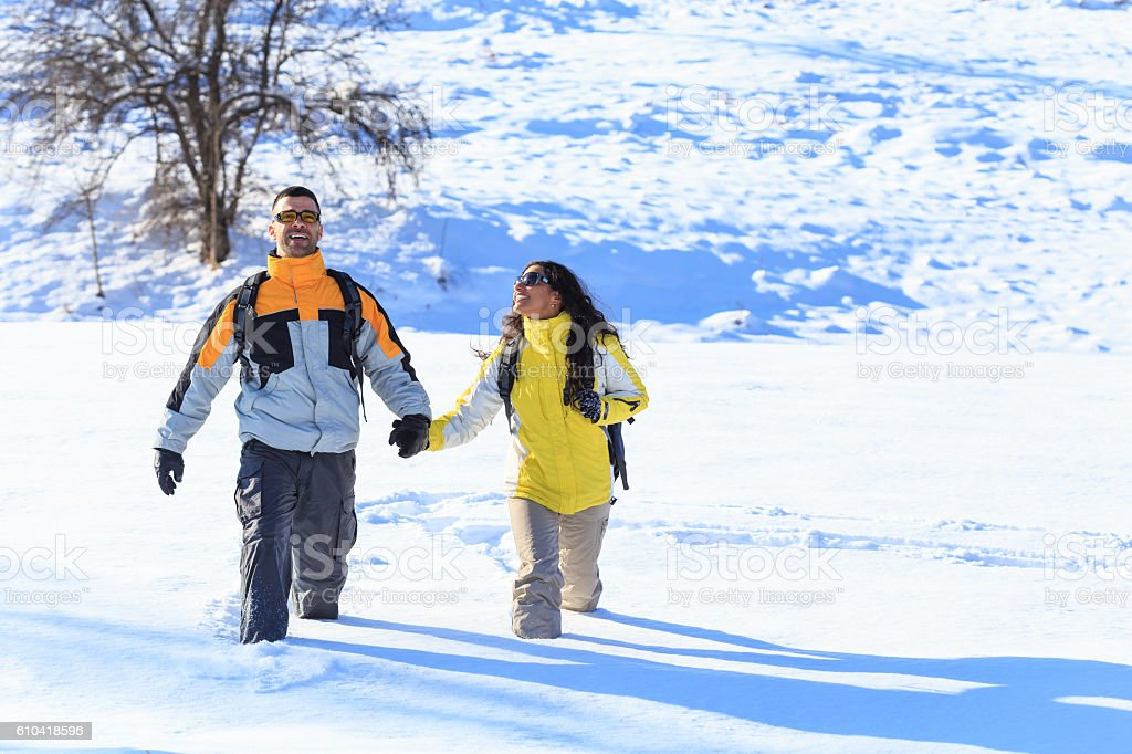 Smiling young couple backpackers hiking in the snow stock photo