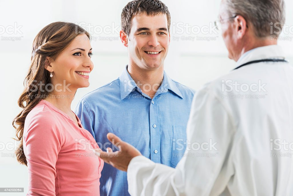 Smiling young couple discussing with mature doctor. stock photo