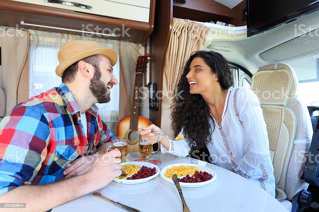 Smiling young couple eating inside of a camper stock photo