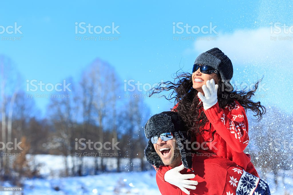 Smiling young couple having fun in the snow stock photo