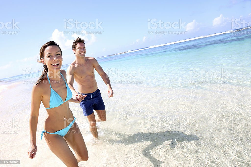 Smiling young couple holding hands on the beach stock photo