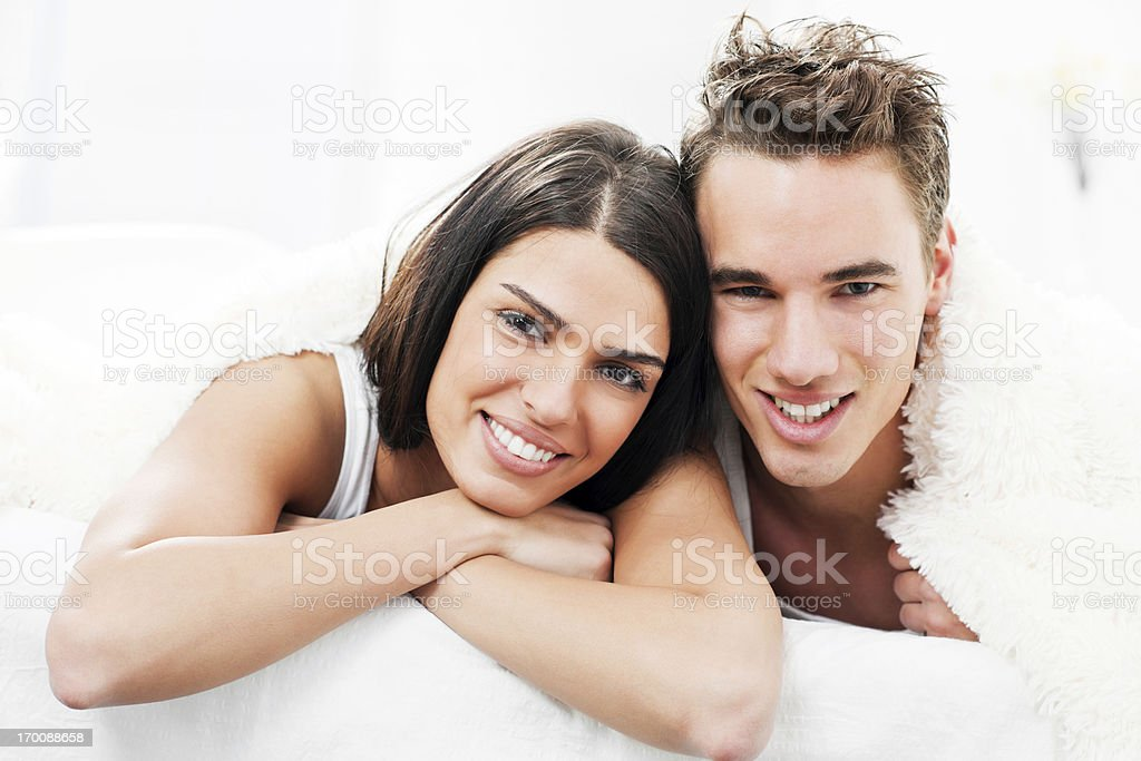 Smiling young couple in bed. royalty-free stock photo