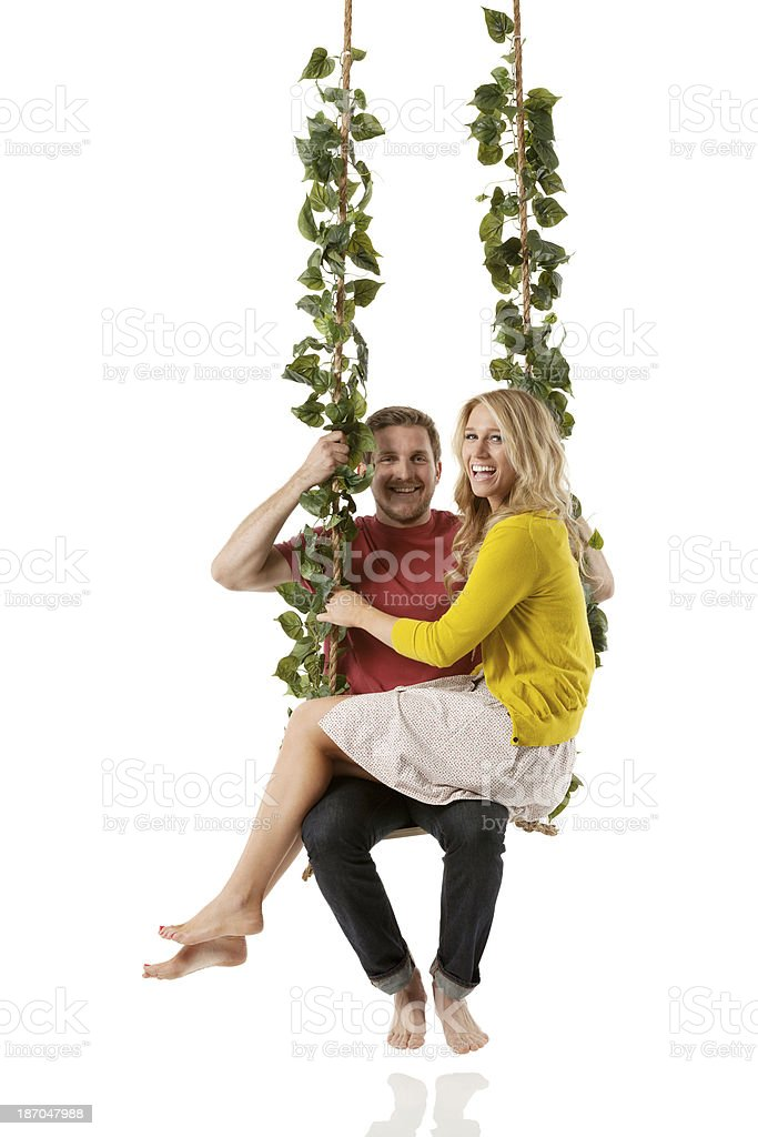 Smiling young couple on ropeswing royalty-free stock photo