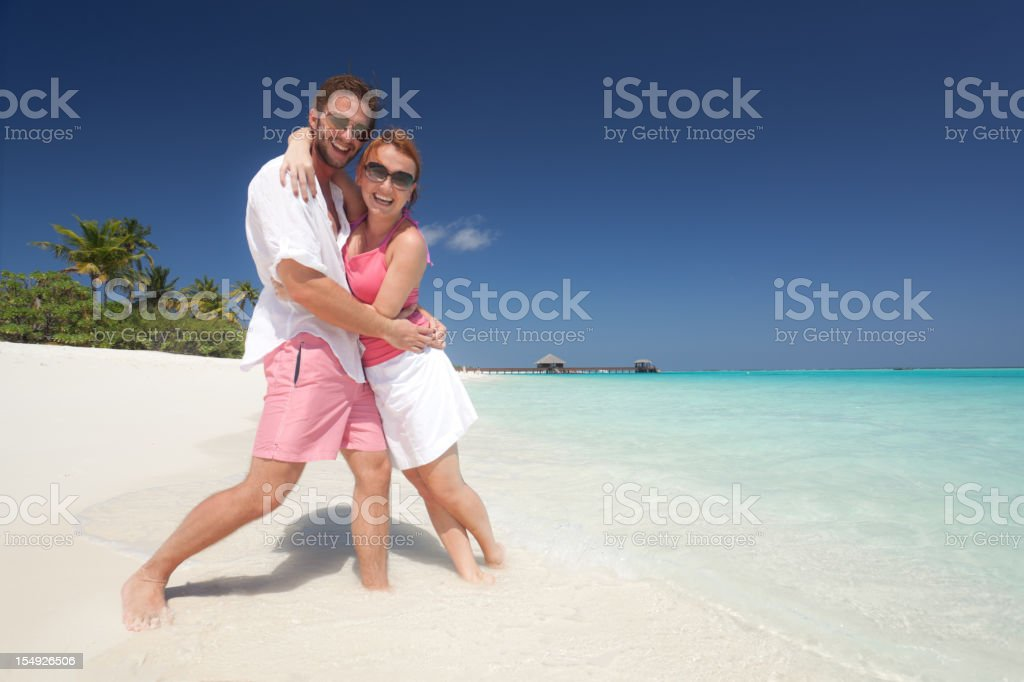 smiling young couple on sandy beach royalty-free stock photo