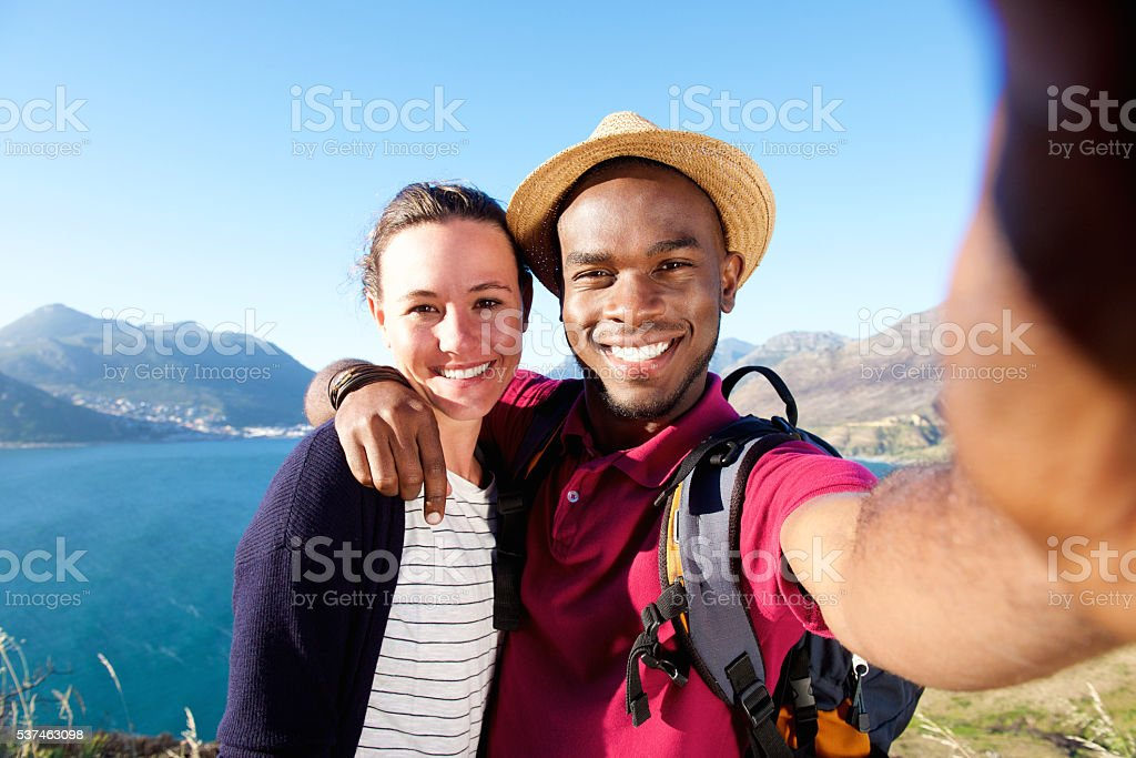 Smiling young couple on vacation taking selfie stock photo