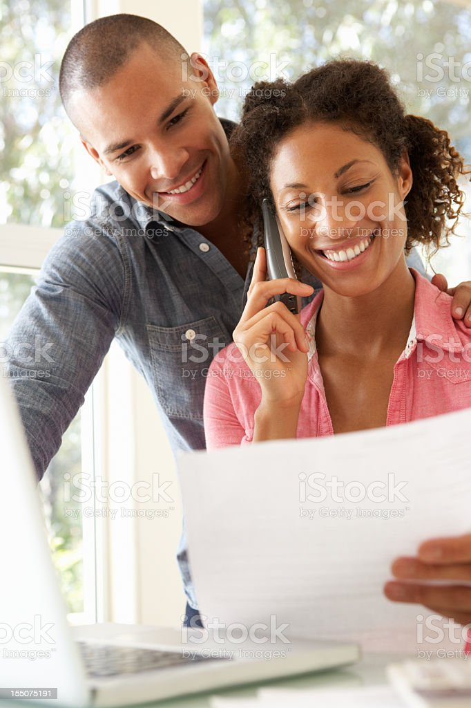 Smiling young couple reviewing documents in front of laptop royalty-free stock photo