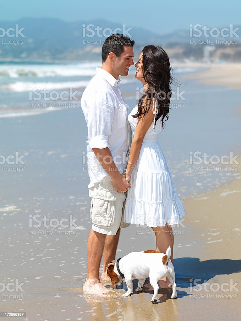 Smiling young couple romancing at beach stock photo