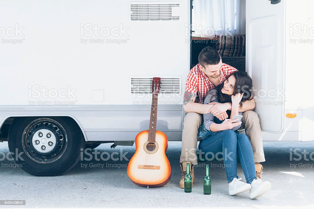 Smiling young couple sitting in front of a camper stock photo
