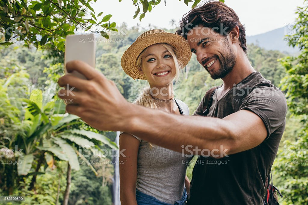Smiling young couple taking selfie with waterfall stock photo