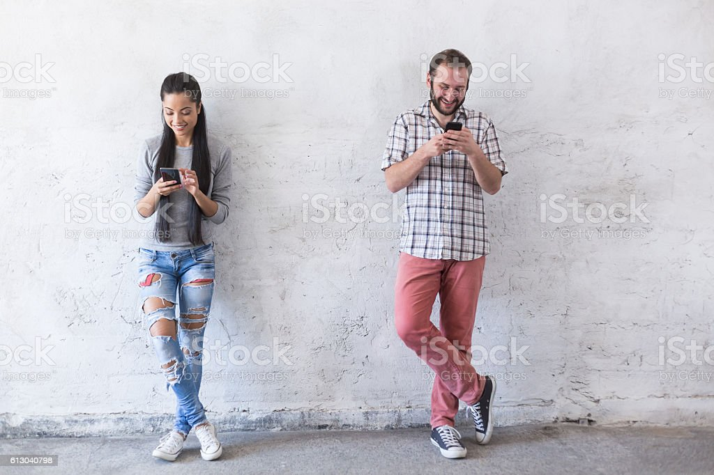 Smiling young couple using smart phones at new empty home stock photo