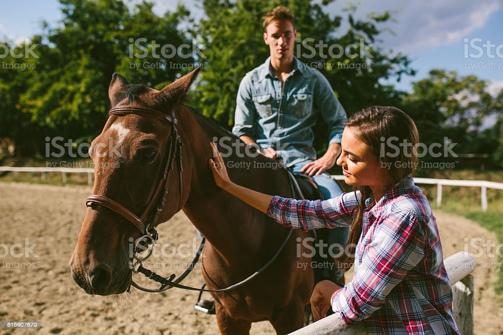 Smiling young couple with horse outdoors. stock photo