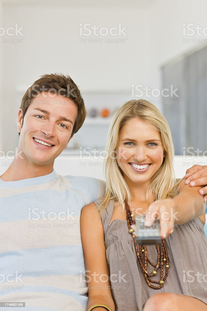 Smiling young couple, woman holding remote control royalty-free stock photo