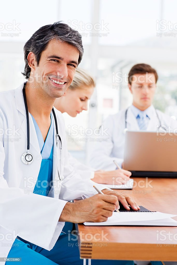 Smiling young doctor with colleagues in background royalty-free stock photo