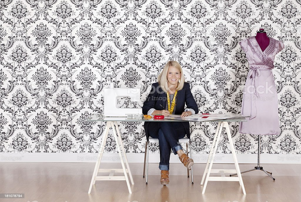Smiling young fashion designer at work royalty-free stock photo