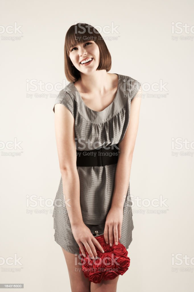 Smiling young fashion model holding red purse stock photo