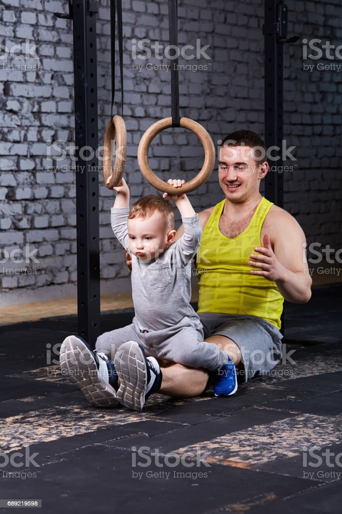 Smiling young father trains the little son with gimnastic rings against brick wall in the gym. stock photo