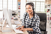 Smiling young female call center worker with headphones