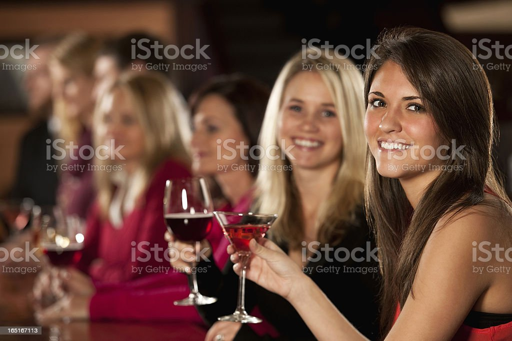 Smiling Young Female Friends Enjoying Drinks stock photo