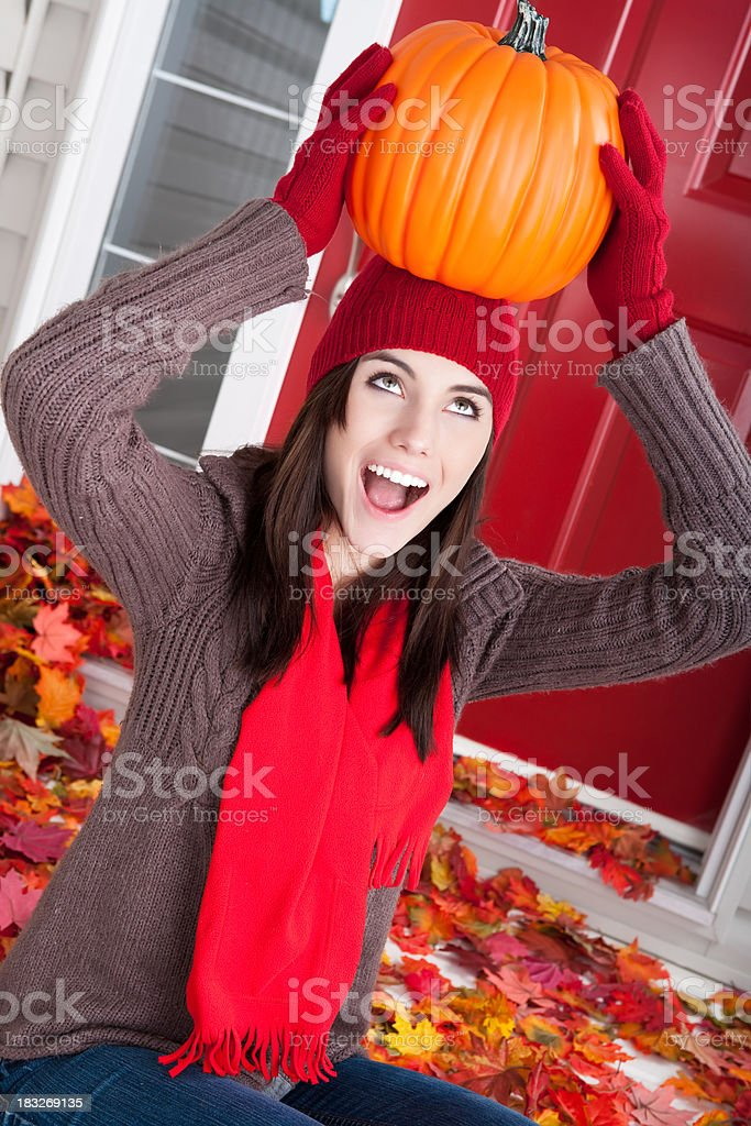 Smiling young female holding a pumpkin on head stock photo