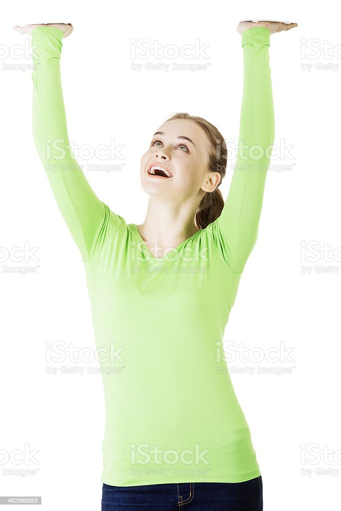 A smiling young female holding her hands above her head stock photo