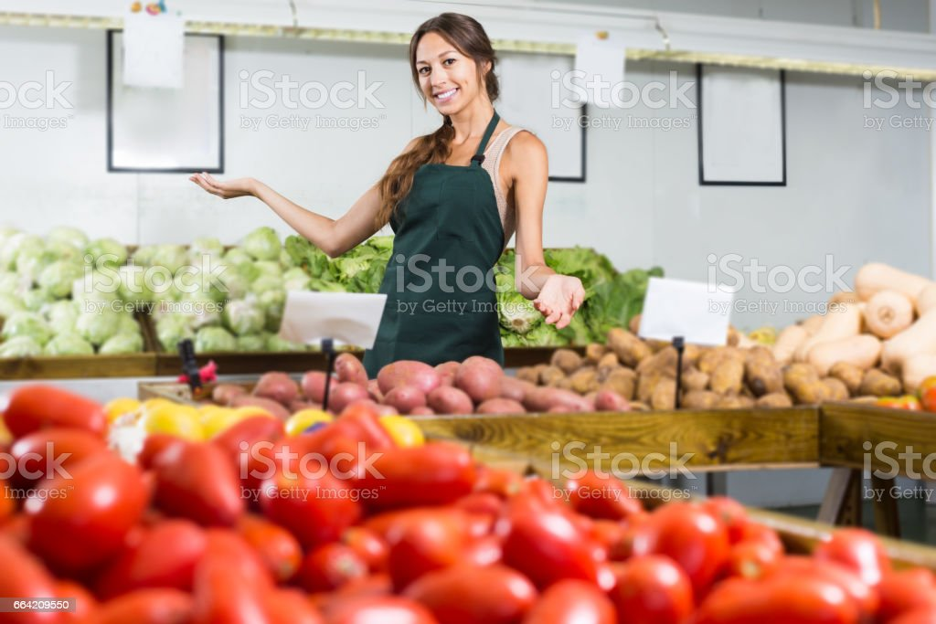 Smiling young female holding potatoes and working stock photo
