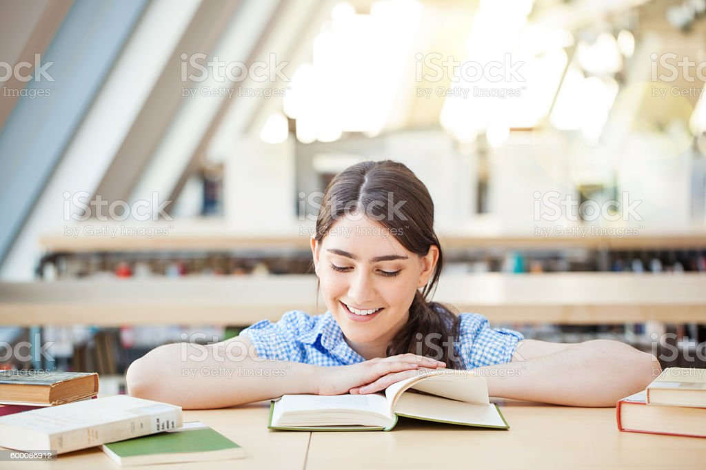 Smiling young female student reading book in a library stock photo