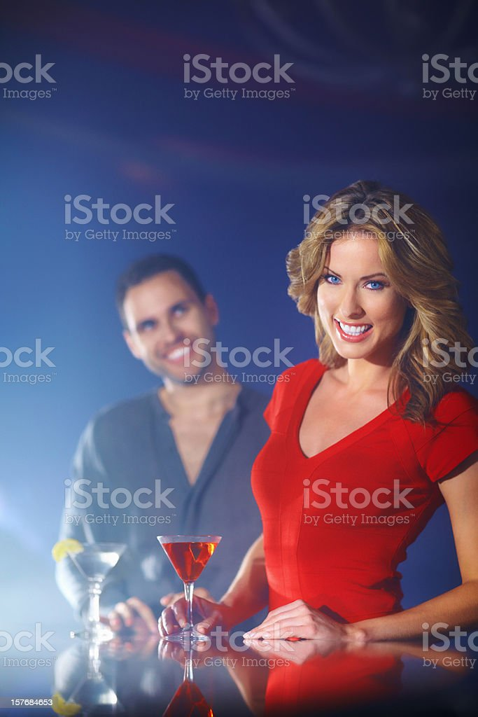 Smiling young female with martini glass and man in background royalty-free stock photo