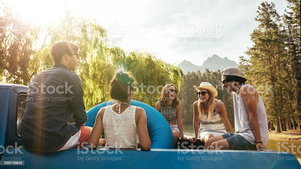 Smiling young friends going on a holiday stock photo