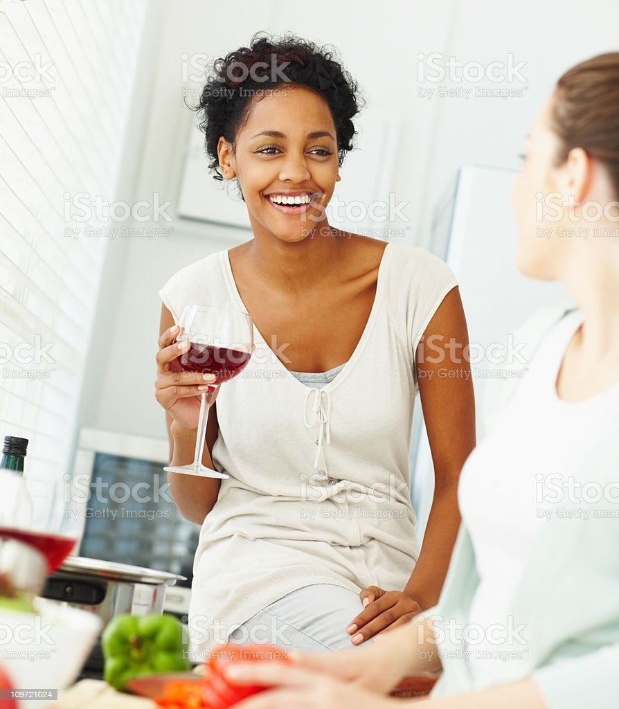 Smiling young friends having a chat while preparing food royalty-free stock photo