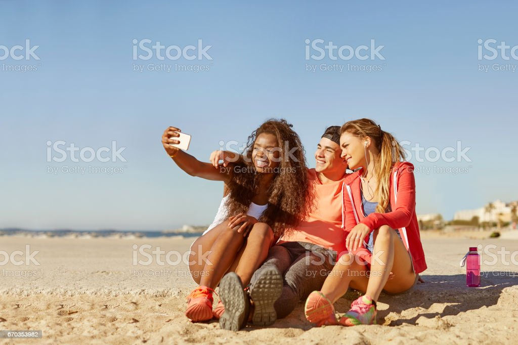 Smiling young friends talking selfie on beach stock photo