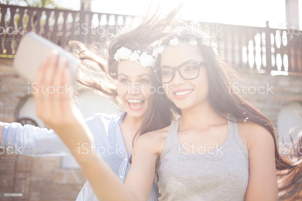 Smiling young friends with wreath making selfie stock photo