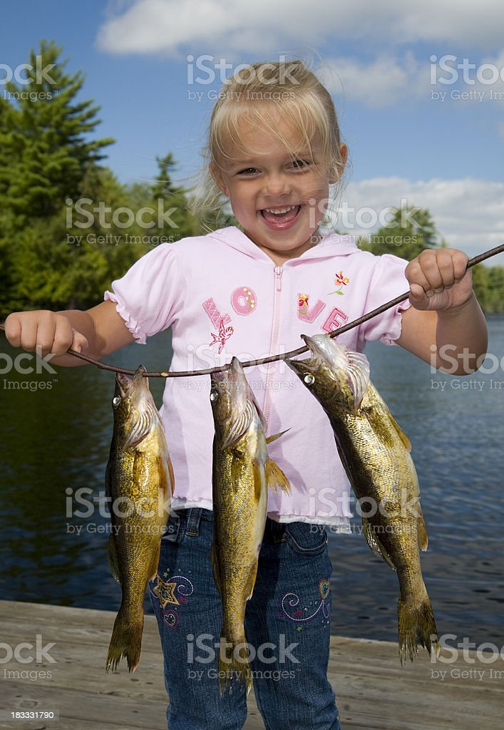Smiling young girl holding a line with three fish royalty-free stock photo