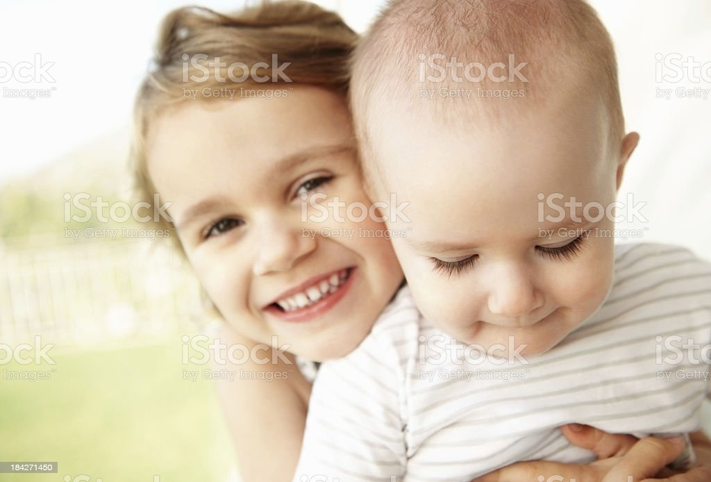 Smiling young girl holding baby royalty-free stock photo