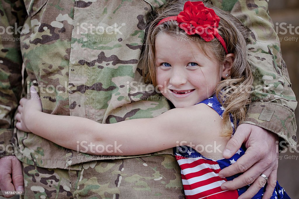 A smiling young girl hugging her soldier father stock photo