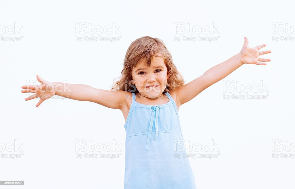 Smiling young girl in a blue dress with arms outstretched stock photo