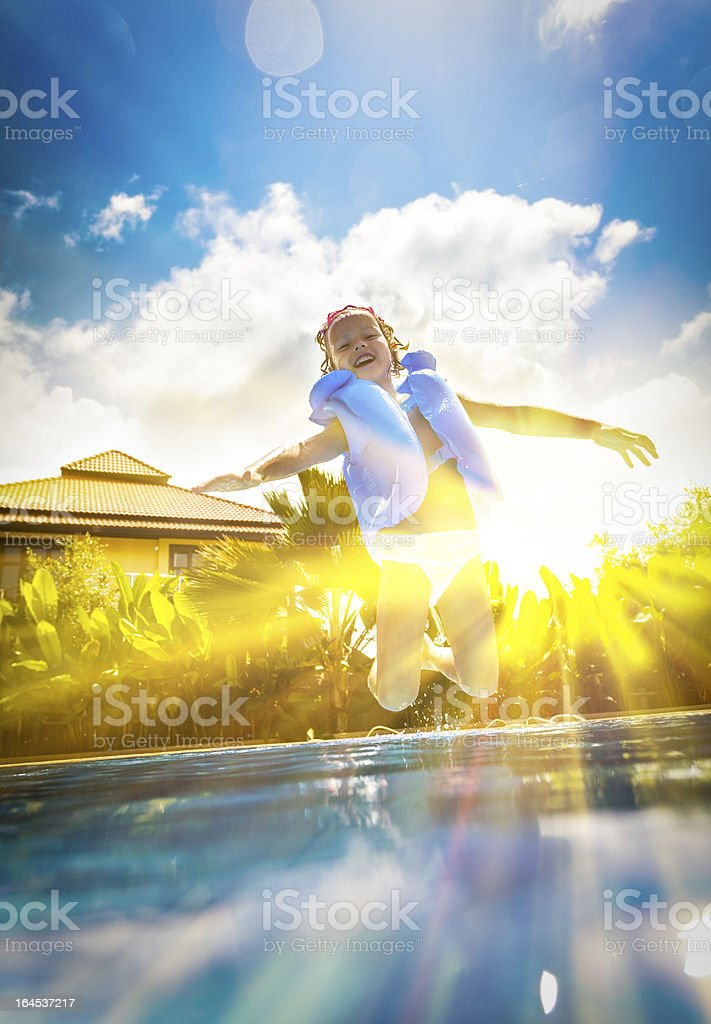 Smiling young girl jumping into swimming pool outside royalty-free stock photo